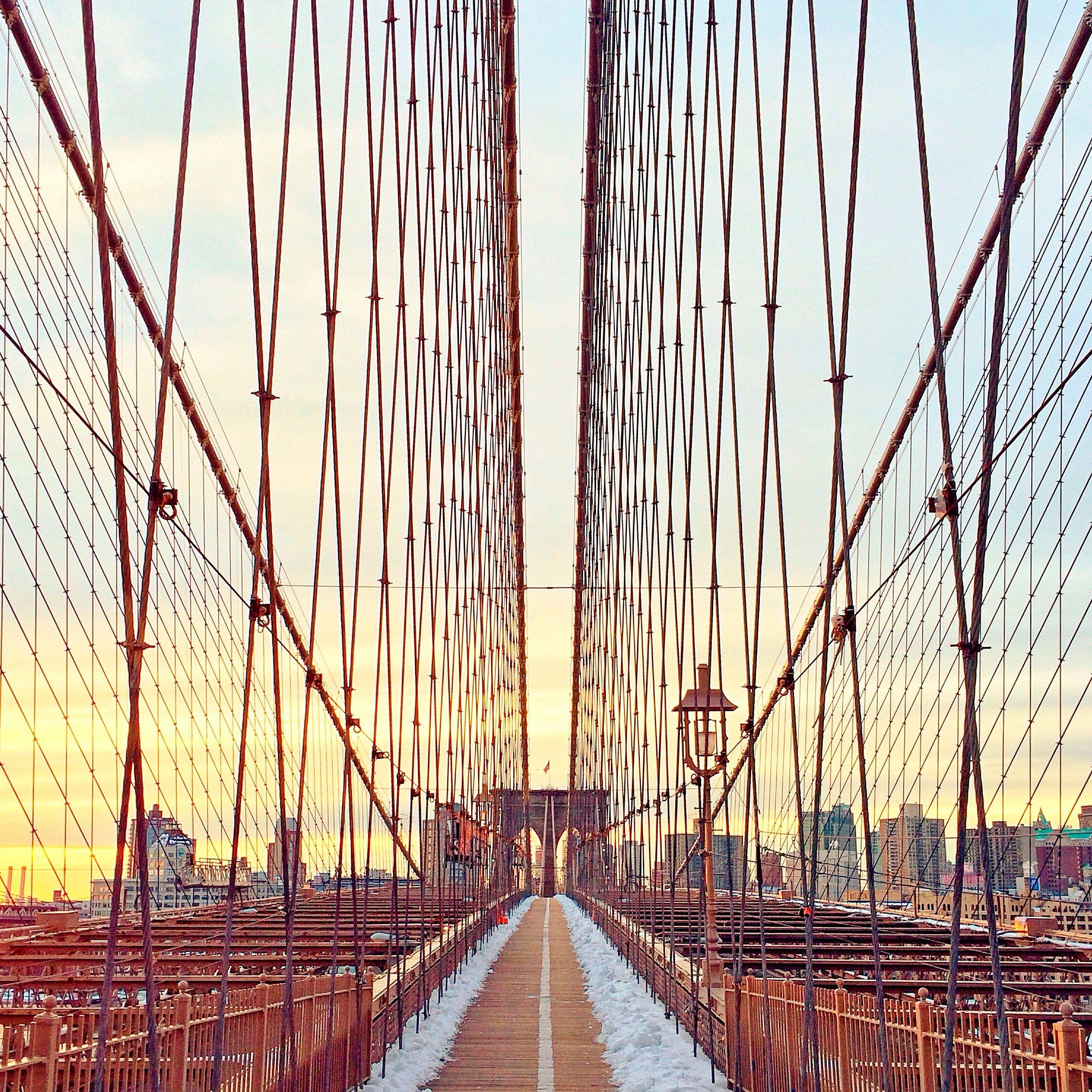 Un pod mare cu orizontul orașului New York în fundal pe măsură ce apune soarele