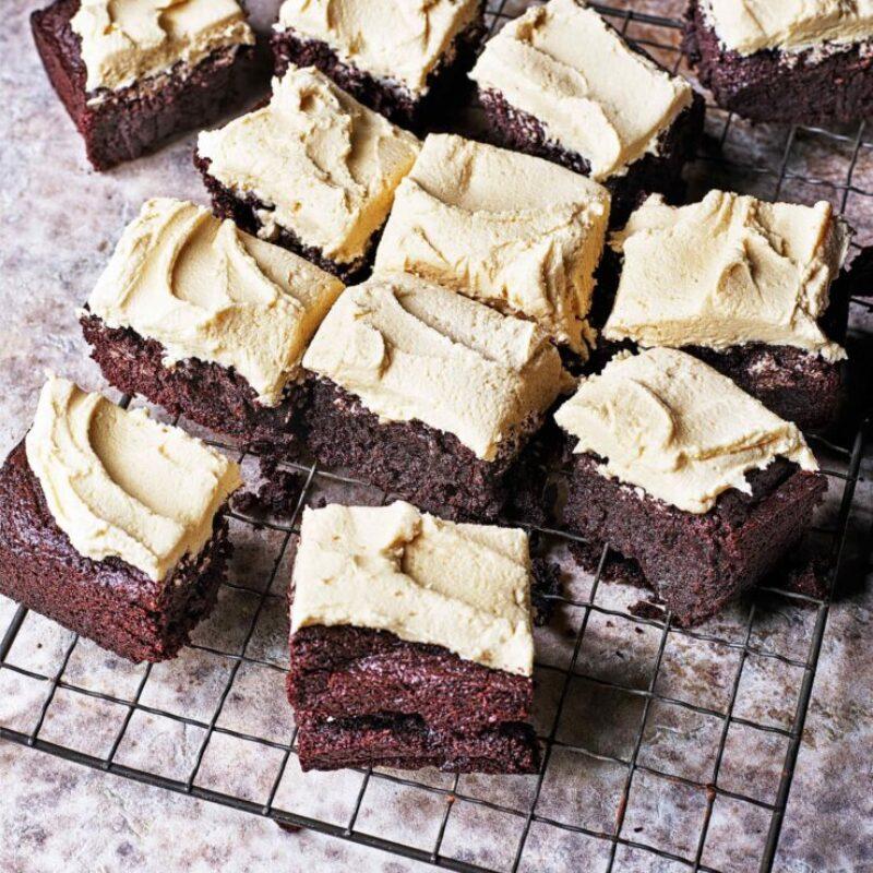 Pătrate de brownies de ciocolată maro, acoperite cu cremă de unt, stăteau pe o tavă de răcire din metal