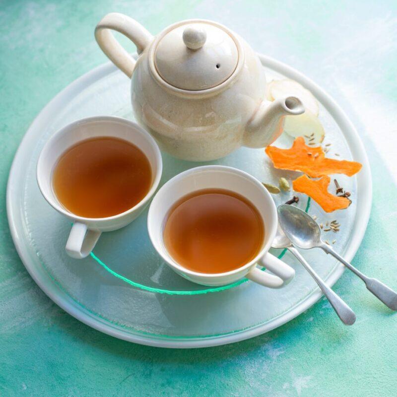 Ceai Turmeric Chai în două căni cu o ceainic