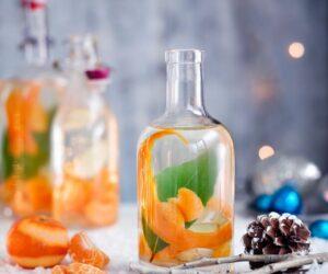 Rețetă de Crăciun Gin cu clementină, ghimbir și dafin pe o masă acoperită de zăpadă cu conuri de pin și segmente de clementină