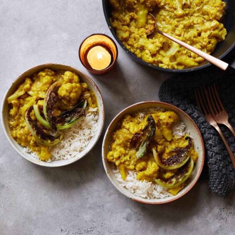 Două boluri de conopidă curry cu orez, așezate una lângă cealaltă cu un set de tacâmuri în dreapta