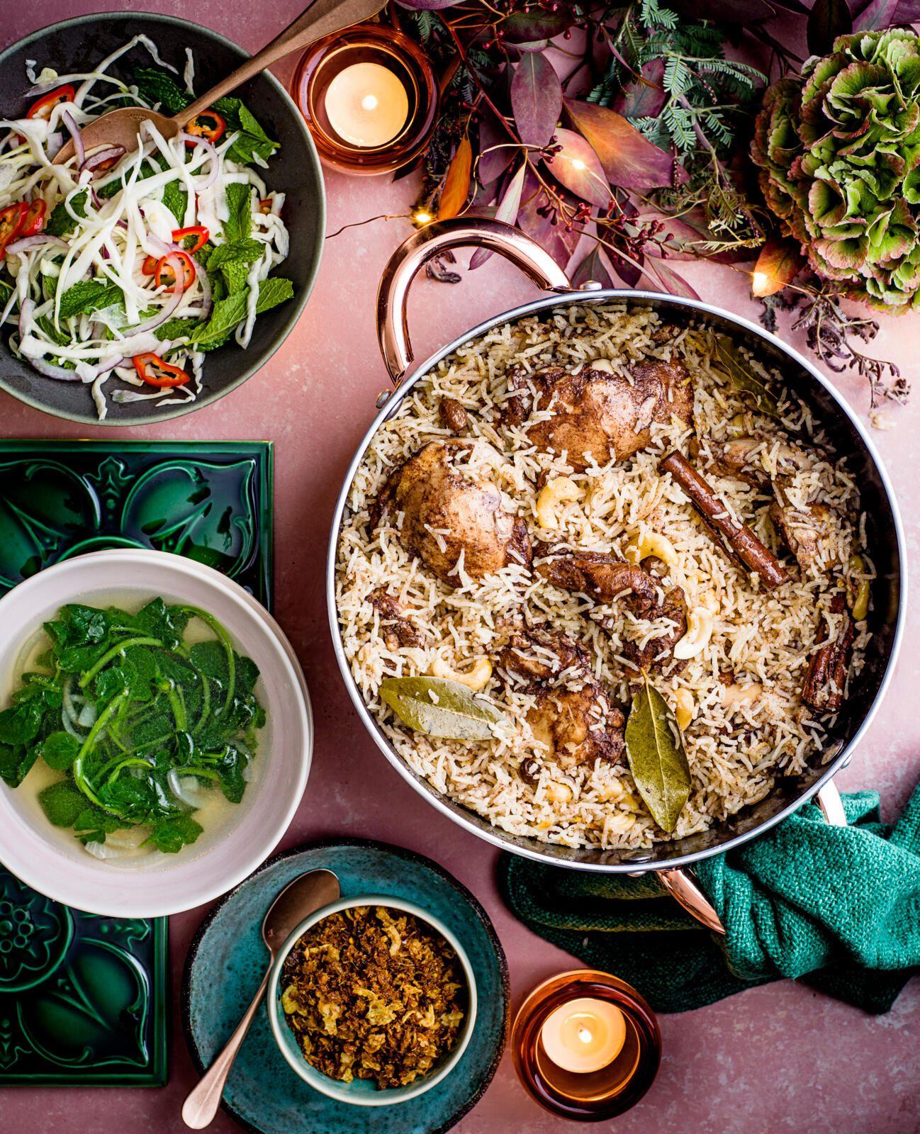 O tigaie imensă plină de coapse de pui fript și orez cu garnituri în jurul său