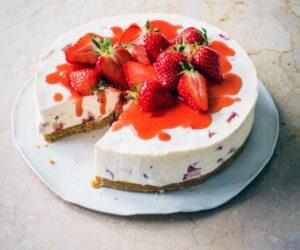 Un tort de brânză alb acoperit cu căpșuni roșii și căpșuni întregi pe o farfurie albă