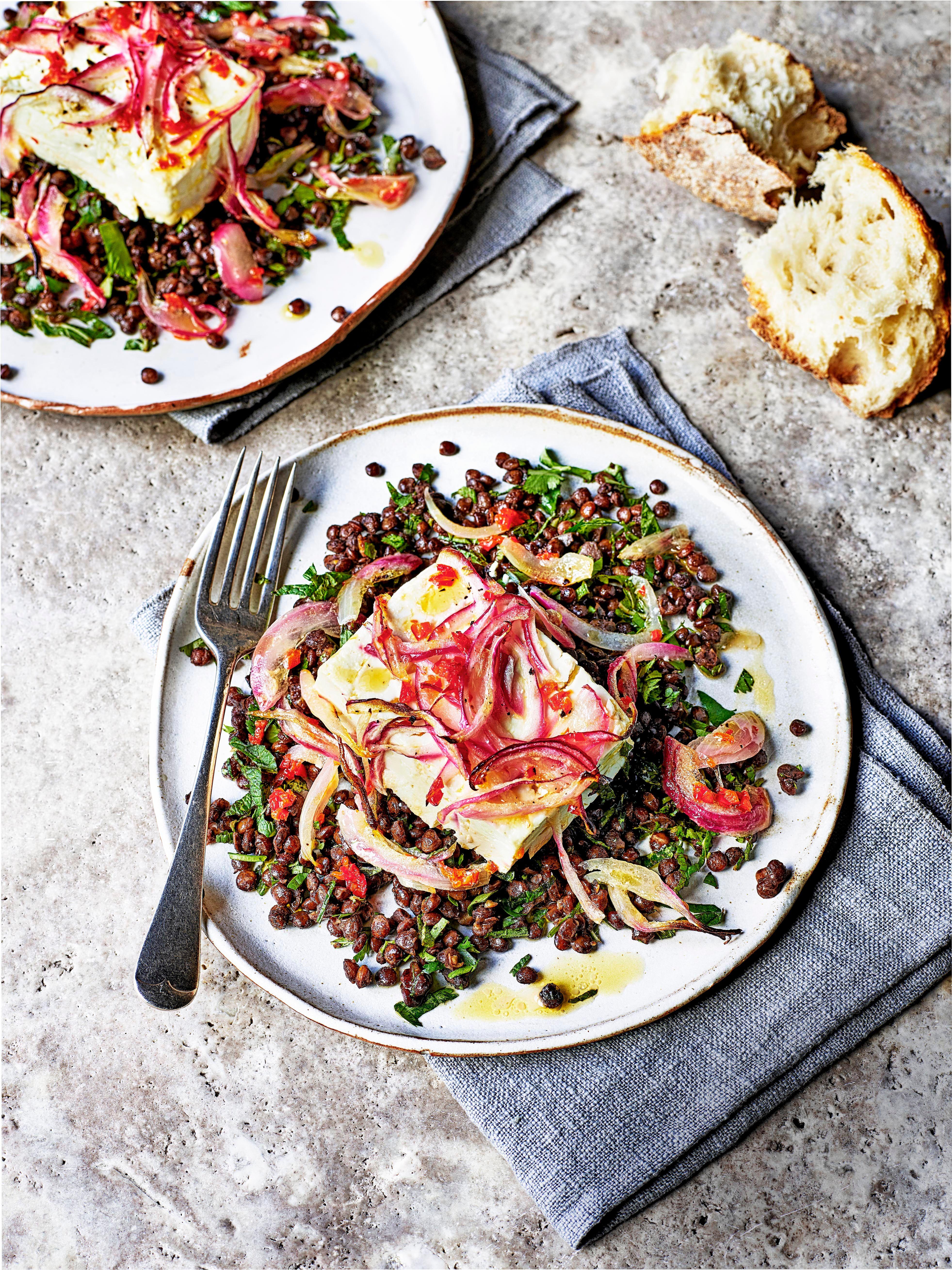 Rețetă de salată de linte cu Feta și pâine crocantă.  Servit pe o farfurie albă cu un șervețel albastru pe o masă gri.