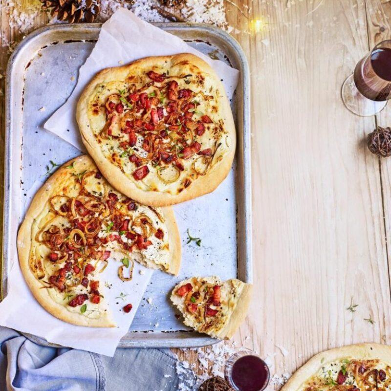 O fotografie aeriană a două pizza cu pâine plată, acoperite cu slănină