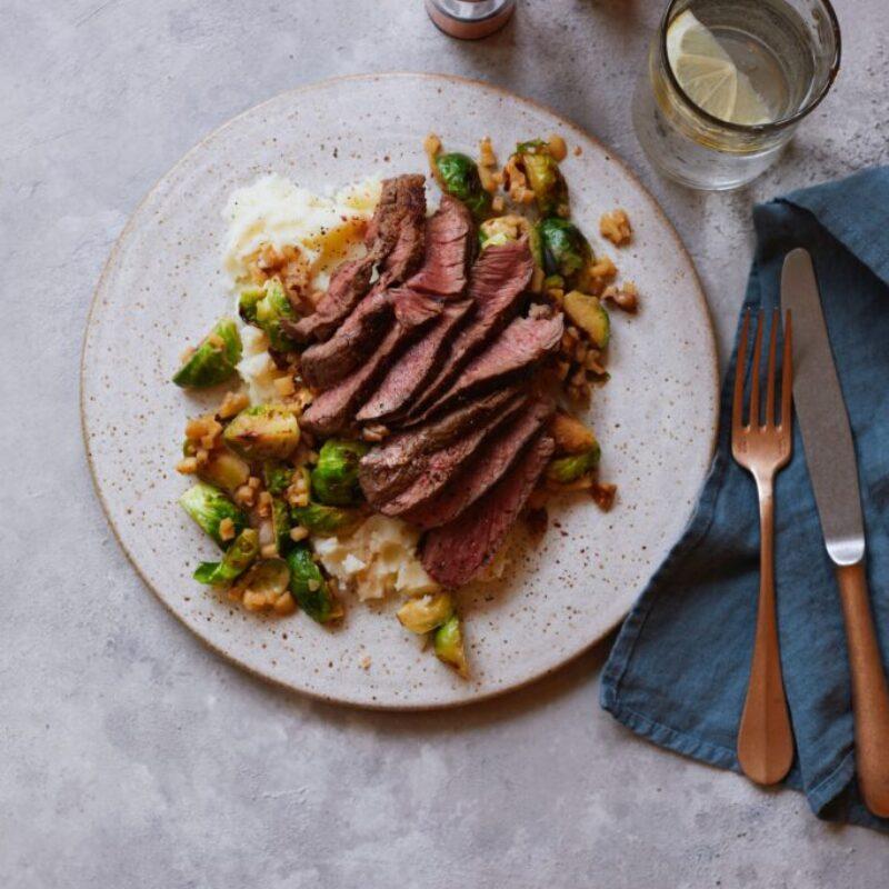 O farfurie pătată de carne tăiată feliată subțire cu varză de Bruxelles, cartofi și nuci