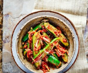 Castravete Kimchi feliat în jumătate cu kimchi presărat deasupra, servit într-un castron albastru și gri adânc pătat
