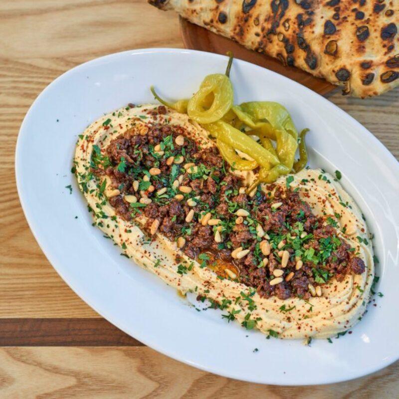 Miel condimentat Baharat, hummus, nuci de pin, stafide și pâine plată