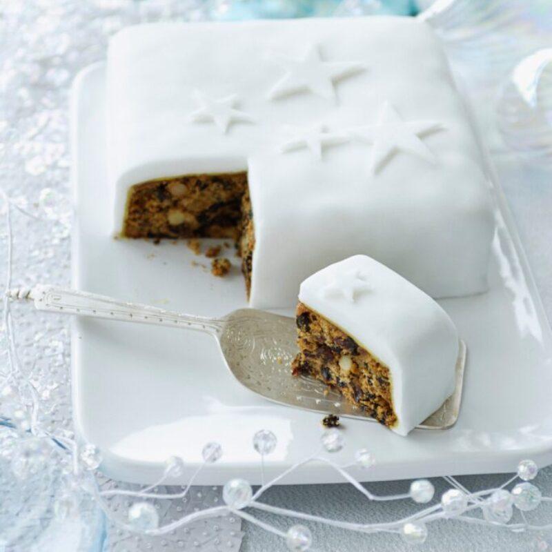 O prăjitură cu fructe acoperită cu glazură albă cu o felie scoasă din ea