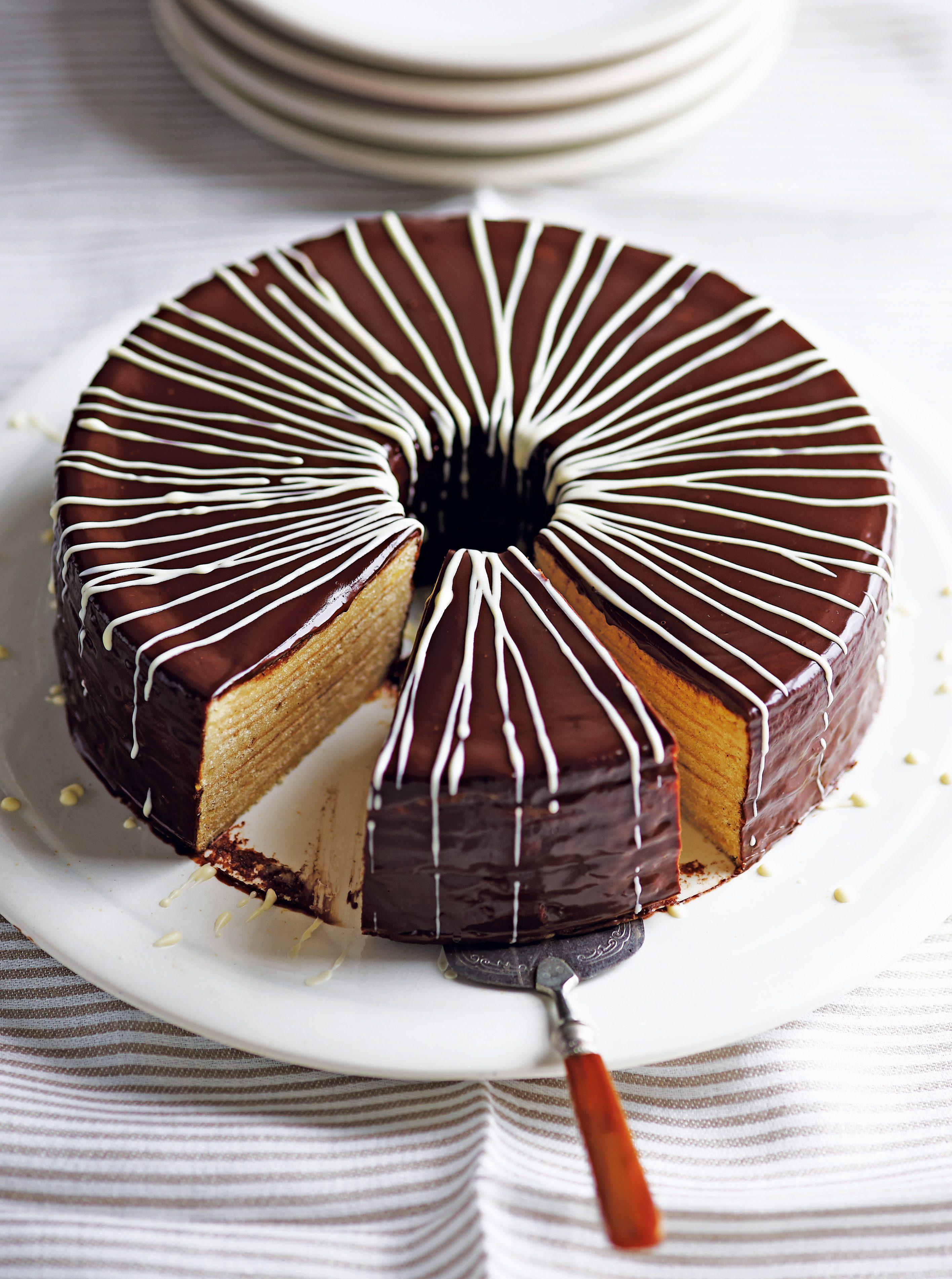 Rețetă de prăjitură cu rom condimentat Bamkuchen - tort de Crăciun german stratificat acoperit cu glazură de ciocolată și linii de ciocolată albă