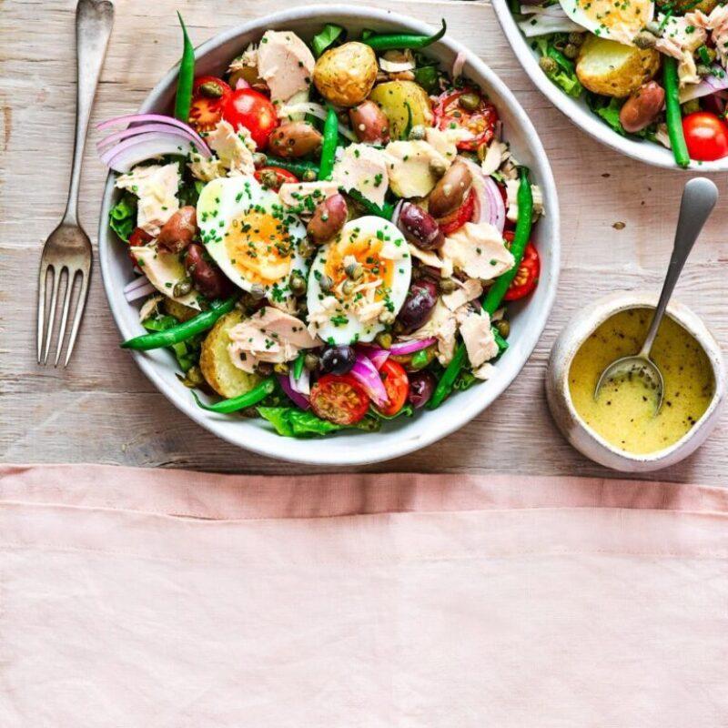 Bol de salată de ton Niçoise lângă oală de muștar cu muștar