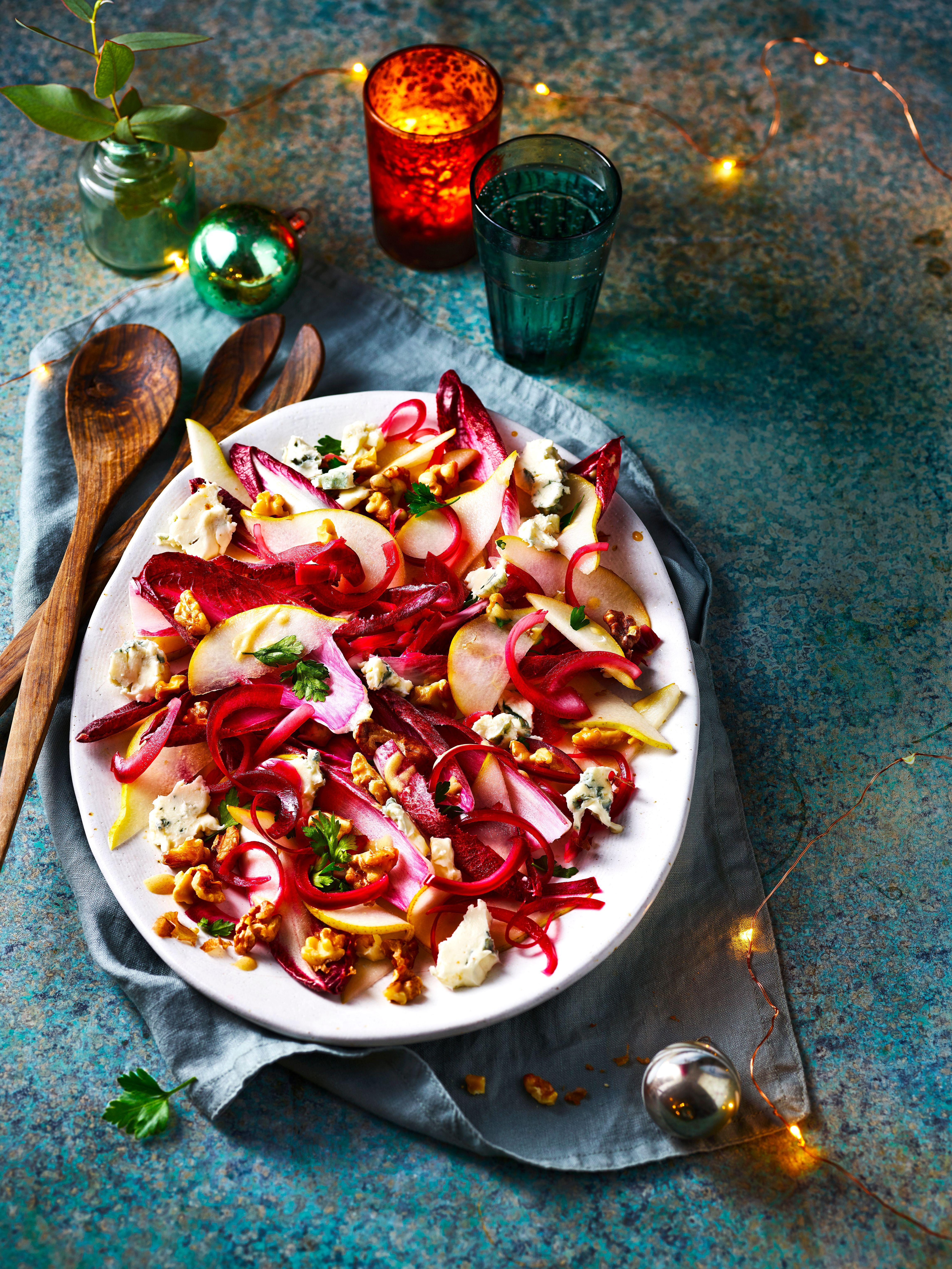 O salată colorată de brânză albastră, cicoare, ceapă roșie și pere, cu linguri de servit din lemn pe o parte
