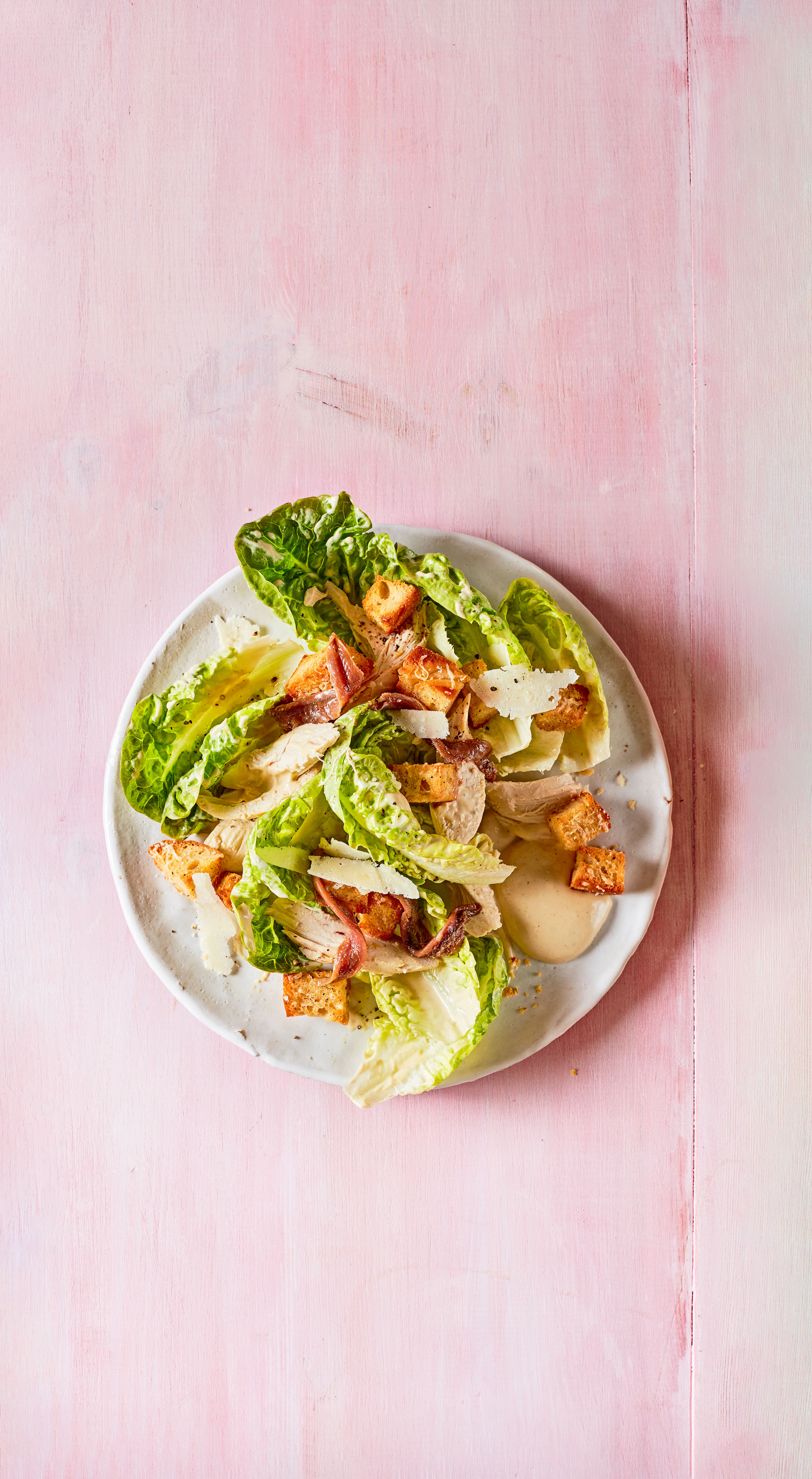 O farfurie de salată albă cu frunze de salată și crutoane