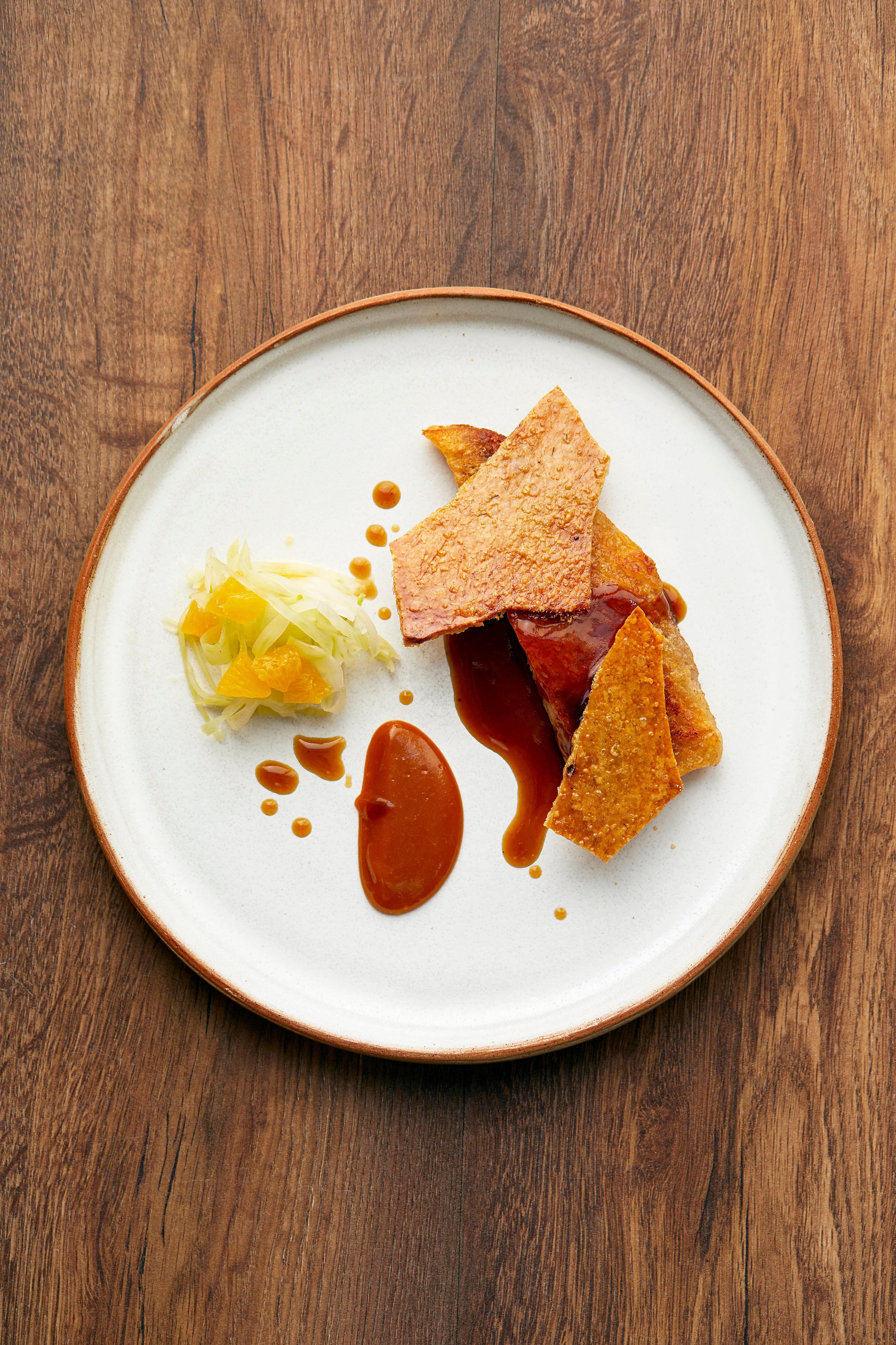Rețetă de porc Jowl cu o salată de fenicul servită pe o farfurie rotundă de culoare alb murdar pe o masă din lemn închis la culoare
