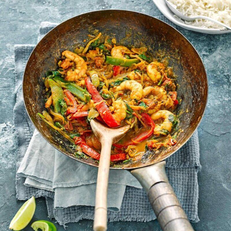 Un wok argintiu este umplut cu creveți, ardei tocați și legume verzi