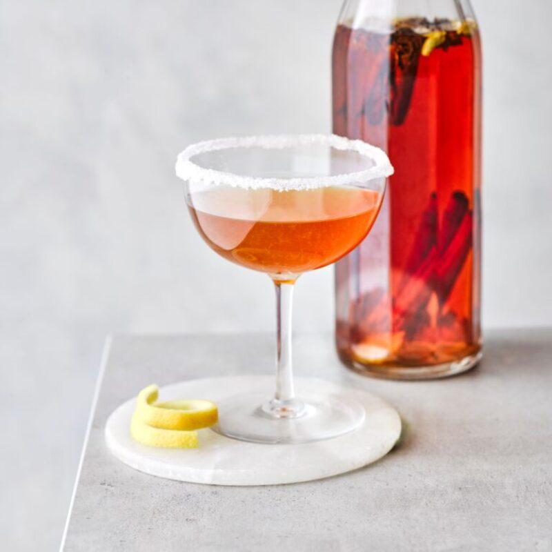 Cocktail sidecar într-un pahar coupe cu o sticlă de lichid roșu în spate
