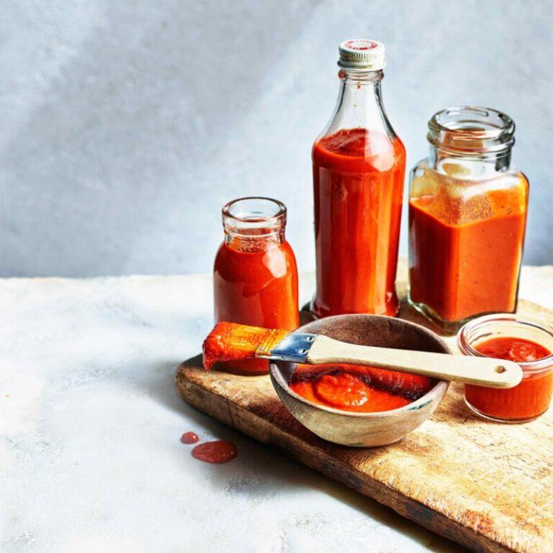Trei sticle de sticlă și un mic vas de lemn, toate umplute cu un sos roșu vibrant