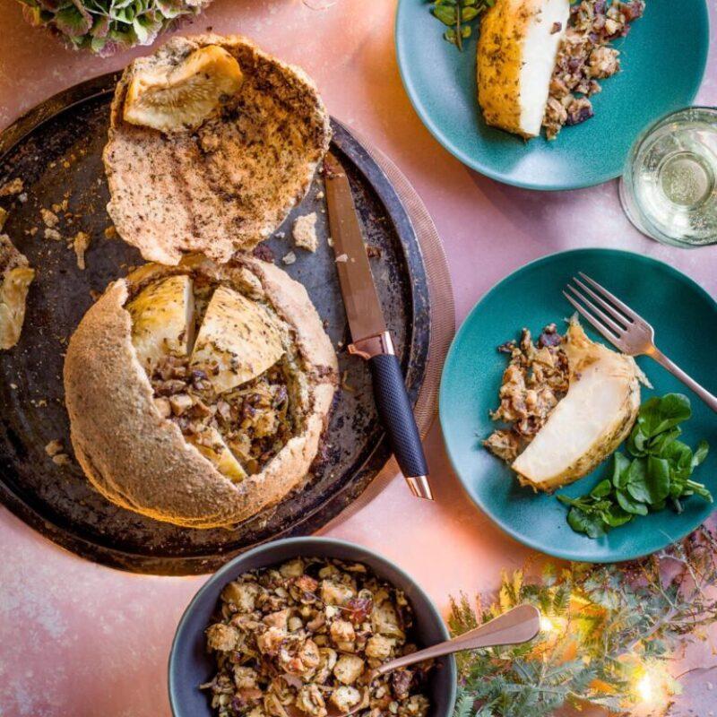 Un țelină întreg într-o crustă de patiserie, cu o farfurie albastră de mâncare așezată lângă ea