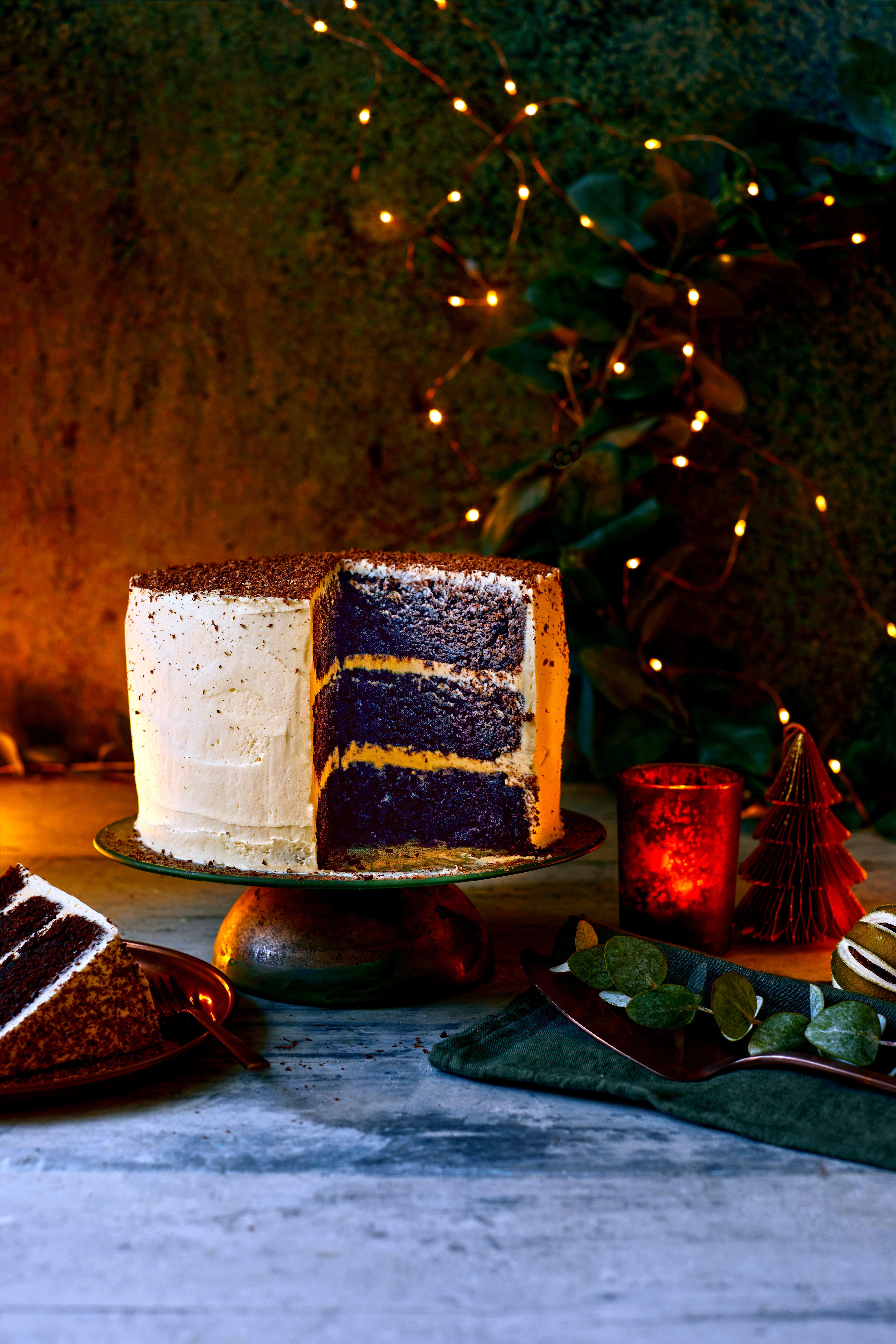 Un tort impresionant cu trei straturi de ciocolată cu gheață, cu lumini de zână în fundal