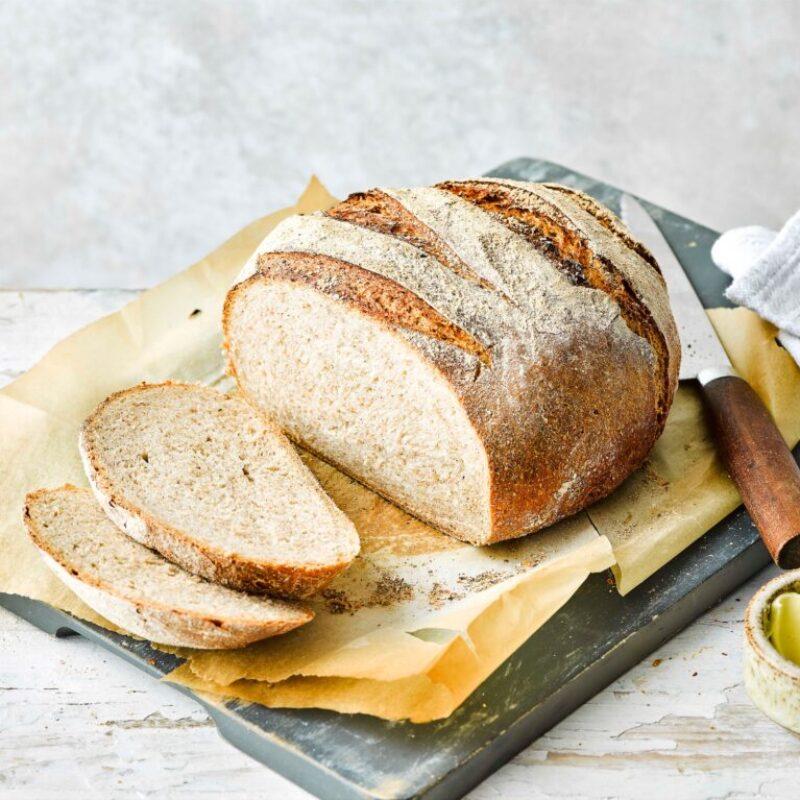 Pâine de secară întunecată feliată cu cuțit și unt